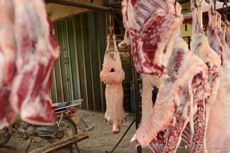 Raw lamb hanging around the market.